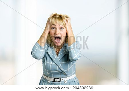 Mature woman in great excitement. Surprised happy white-skin woman looking straight with open mouth and hands on head in astonishment.