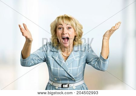 Surprised happy mature woman. Astonished happy white-skin woman looking straight with open mouth and raised hands in excitement.