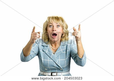 Surprised woman having an idea. Close up portrait of middle aged woman looking surprised and raising both hands with index finger and wide open mouth, white background.