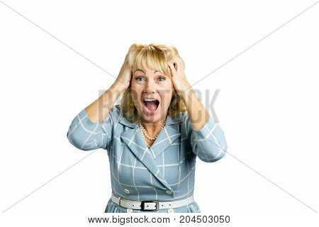 Excited mature woman, white background. Close up portrait of white-skin woman looking surprised in full disbelief with hands on hand and open mouth against white background.