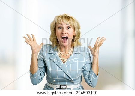 Surprise mature woman with good news. Close up portrait of white-skin woman looking shocked and excited in full disbelief with open mouth and raised hands.