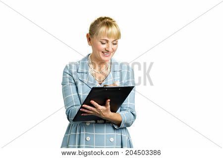 Cheerful woman making a note on clipboard. Mature woman writing on clipboard and smiling isolated on white background.
