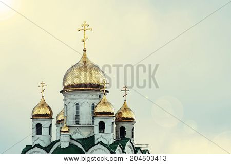 Christian church against the blue sky. Golden domes. Facade.