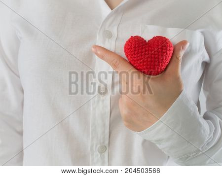 close up of woman in white shirt holding red shape sing on isolated background concept of health care heart disease.