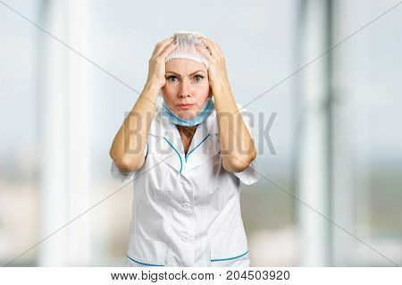 Surprised and confused female doctor. Portrait of white-skin female doctor or nurse surprised starring with scared eyes, blurred background.