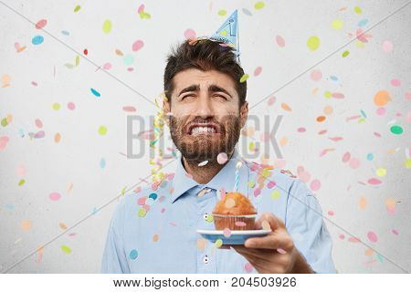 Wretched Young Man Holds Puncake, Going To Cry As Celebrates Anniversary Alone. Gloomy Guy Wears Shi