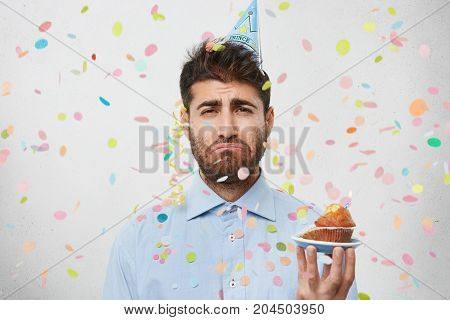 Portrait Of Discouraged Unshaven Man Being Unhappy To Realize That Birthday Party Is Over, Holds Cup