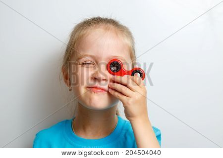 Little girl playing with fidget spinner, on white background