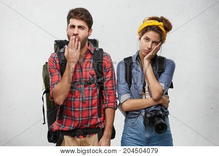 Good Looking Male Backpacker And Female Companion Stand Against White Studio Wall, Hold Rucksack And