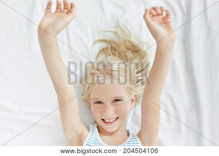 Happy Cute Little Girl With Fair Hair And Freckles Stretching Arms After Sleep, Lying On White Bedcl
