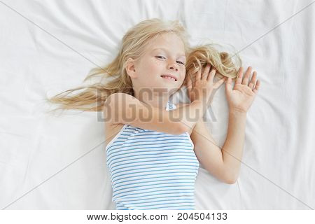 Healthy Sleep And Childhood Concept. Pleased Attractive Female Kid Listens To Fairy Tales Readed By