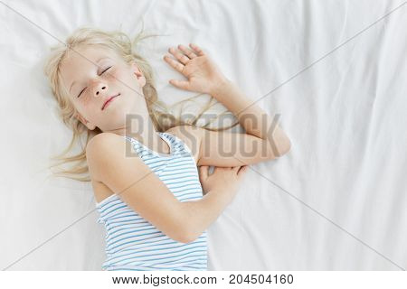 Candid Shot Of Adorable Caucasian Little Girl With Freckles Wearing Sailor Pajamas While Sleeping So