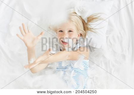 Indoor Shot Of Carefree Little Blonde Girl With Blue Eyes Plays In Bedroom, Catches Feather In Air,