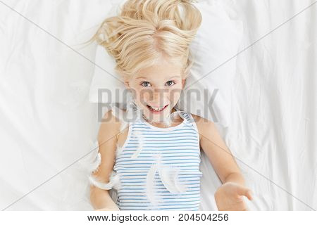 Childhood, Bedtime And Happiness Concept. Freckled Appealing Girl Wears Night Clothes, Plays With Fe