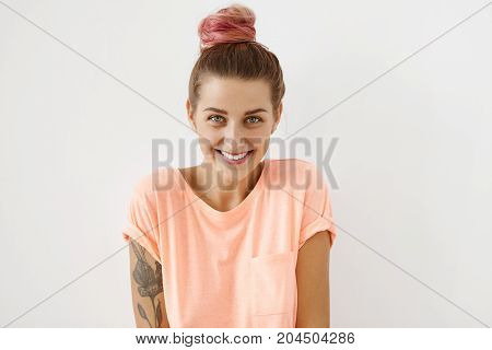 Charming Playful Coquettish Young European Female With Pink Hair Bun Smiling Shyly At Camera As If F