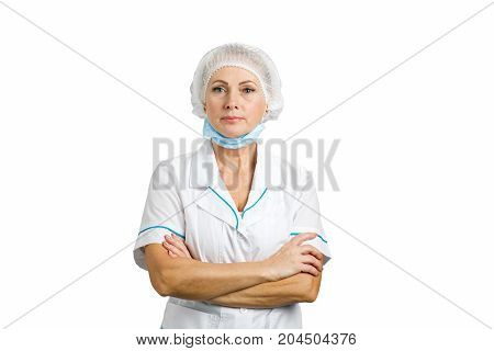 Beautiful medical professional crossed arms. Female doctor surgeon in scrubs with medical hat crossed arms over white background.