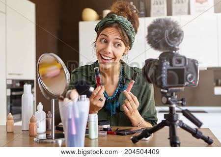 Portrait Of Excited Cheerful Young Woman Vlogger Holding Two Lipsticks Of Different Brands And Compa