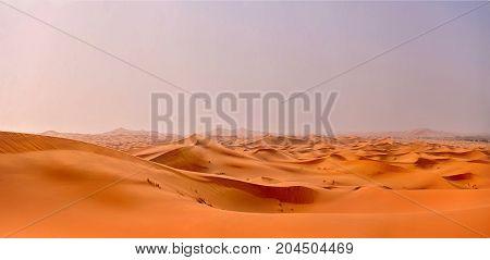 the orange dunes of the Sahara Desert leaving to the horizon. The dawn beginning over the desert