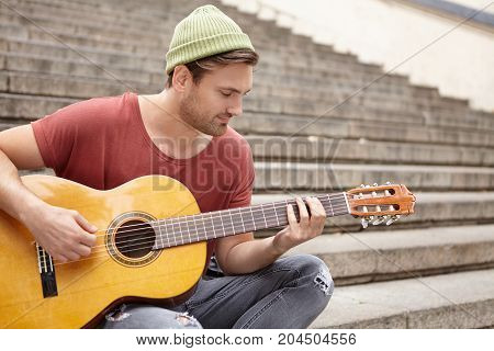 Talented Bearded Street Musician, Demonstrates Endowment, Plays Acoustic Guitar, Sits On Stairs Outd