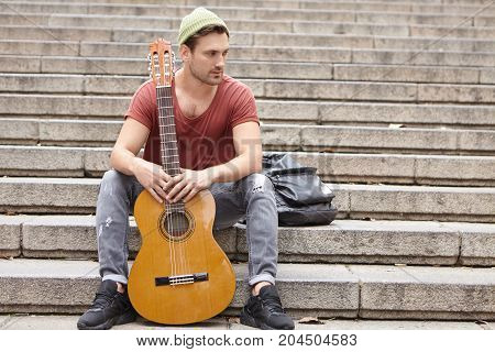 Pensive Stylish Male Singer And Musician, Sits On Stairs With Guitar, Dreams About New Musical Instr