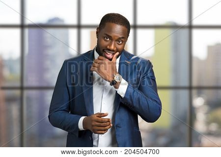 Afro american businessman touching chin. Smiling young black man with hand near his chin. Black boss of corporate company on blurred background.