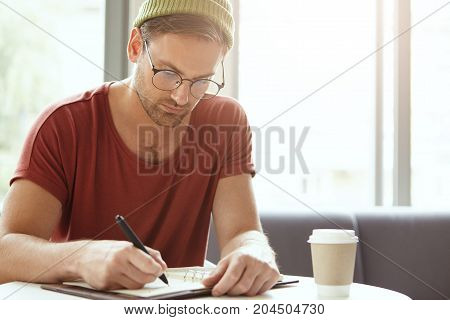 Young Talented Copywriter Puts Down Ideas In Notebook, Sits At Coffee Shop, Looks Seriously At Notes
