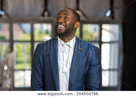 Looking upward and smiling businessman. Happy young afro american manager indoors. Natural smile and joy of handsome businessman.