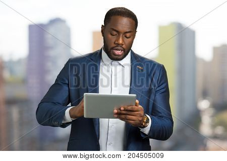 Black businessman with digital tablet. Young entrepreneur speaking and looking at pc tablet. Manager with tablet on blurred background.