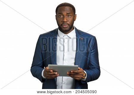 Black businessman looking upset. Young afro american manager hold computer tablet and look straight. Darkskinned executive director surprised with bad news.
