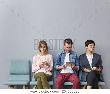 People employment recruitment technology concept. Three unemployed people sit in queue wait for job interview use modern gadgets prepare answers on tricky questions from boss or employer
