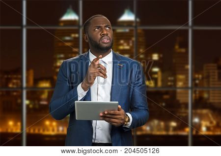 Young businessman on evening background. Serious black man in formal wear hold computer tablet and worriedly thinking looking upward.