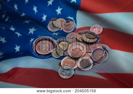 A pile of coins lie in the water on an American flag