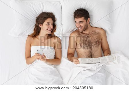 Happy Loving Couple In Bedroom: Bearded Handsome Man Reads Newspaper And His Wife Surfes Social Netw
