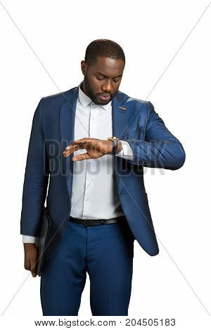 Black businessman looking on wrist watch. Afro american manager checking time on white background. Punctuality and responsibility of young businessman.