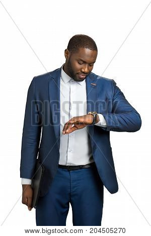 Businessman looking at his watch. Manager looking at wrist watch and smiling. Positive business person waiting for meeting.