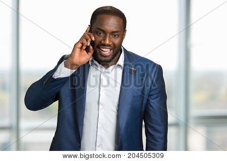 Happy black businessman making a call. Young afro american guy speaking on cellphone and smiling. Positive communication in office on mobile.