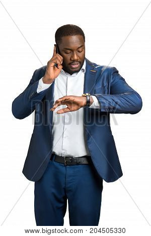 Successful businessman hurry on meeting. Serious afro american manager looking at watch and speaking on phone. Busy executive in suit on white background.