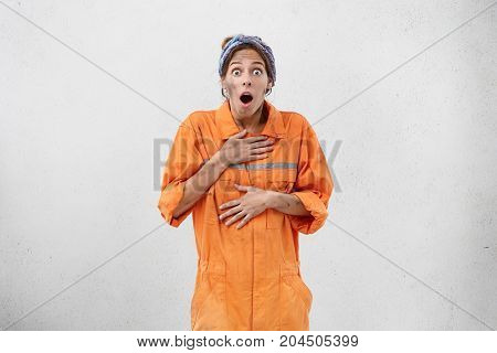 Shock And Astonishment Concept. Funny Young Woman From Maintenance Service Dressed In Orange Uniform