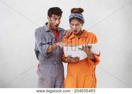 Portrait Of Two Carpenters Look At Blueprint With Bugged Eyes, Being Shocked To See Damage Or Fault.