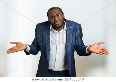 Black businessman shrugging shoulders. Afro american manager showing gesture I do not know, body language.