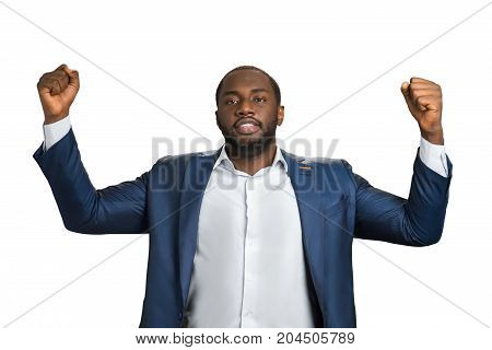 Businessman clenching raised fists. Young black man demonstrate his power and victory with raised hands. Happy businessman celebrating his success.