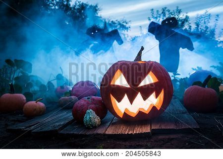 Spooky Pumpkin With Scarecrows On The Field For Halloween