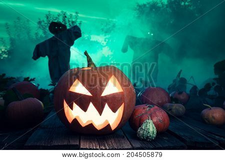 Glowing Halloween Pumpkin With Green Mist And Scarecrows