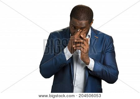 Business man wipe his eye. Afro american young manager in dark blue suit wipe eye with white napkin.