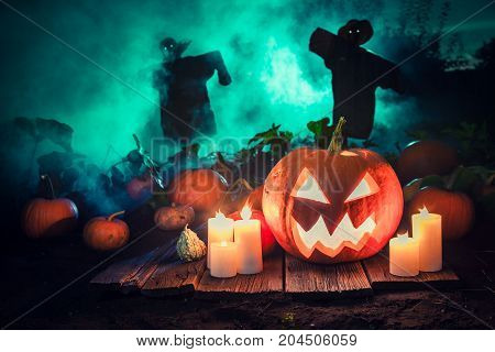 Spooky Pumpkin With Green Mist And Scarecrows For Halloween