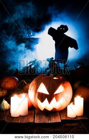 Spooky Pumpkin On Dark Field With Scarecrows For Halloween