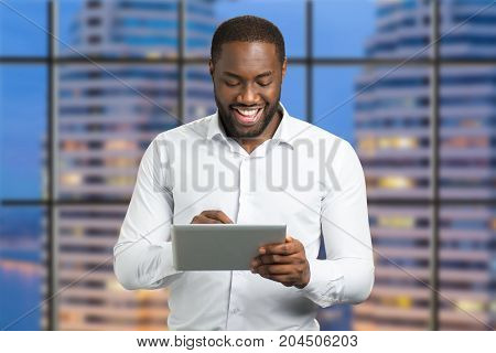 Afro american happy smiling manager. Businessman on evening city background read news on pc tablet and smiling.