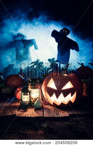 Scary Halloween Pumpkin With Blue Mist And Scarecrows