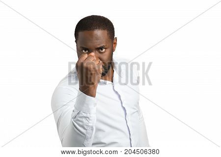 Aggressive black businessman shaking fist. Angry businessman shaking fist on white background. Irritated dark skinned businessman.