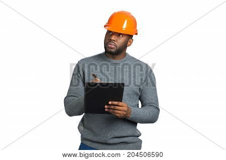 Serious architect with hardhat and clipboard. Builder man working with black clipboard in a protective helmet.